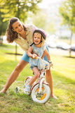 Mother and baby girl with bicycle Royalty Free Stock Image