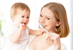 Mother and  baby girl brushing  teeth together Stock Photos