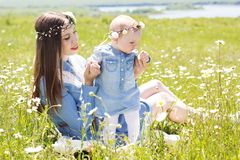 Mother with baby girl on the camomile meadow Stock Photos