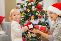 Mother and baby girl changing Christmas presents Royalty Free Stock Photography