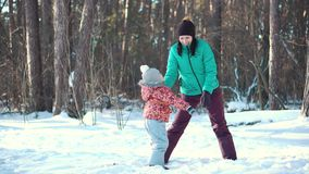 Mother and baby girl daughter playing and laughing in winter outdoors in the snow stock footage