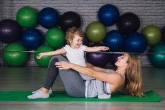 Mother and baby girl do exercises together in the gym. Young sporty mother and baby girl do exercises together in the gym. Parent and child healthy development Royalty Free Stock Photo