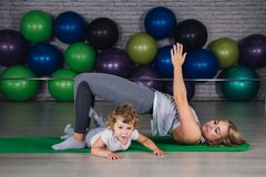 Mother and baby girl do exercises together in the gym stock photo