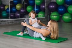 Mother and baby girl do exercises together in the gym. Young sporty mother and baby girl do exercises together in the gym. Parent and child healthy development Stock Images