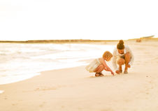 Mother and baby girl drawing on sand on beach Stock Image