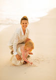 Mother and baby girl drawing on sand on beach Royalty Free Stock Images