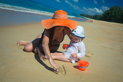 Mother with baby girl drawing on sandy beach Royalty Free Stock Photo