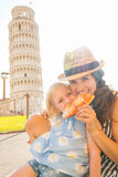 Mother and baby girl eating pizza in pisa. Happy mother and baby girl eating pizza in front of leaning tower of pisa, tuscany, italy Royalty Free Stock Images