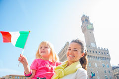 Mother and baby girl with flag in front of palazzo Royalty Free Stock Image
