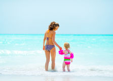 Mother and baby girl going into sea Stock Photos