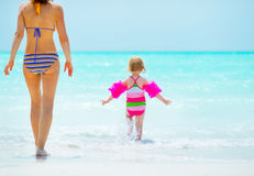Mother and baby girl going into sea. rear view Stock Image