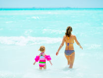 Mother and baby girl going into sea. rear view Stock Images