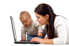 Mother and baby girl having fun with laptop Stock Photos