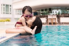 Mother and baby girl having fun in the pool. Summer holidays and Royalty Free Stock Photo