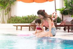 Mother and baby girl having fun in the pool. Summer holidays and. Vacation concept Stock Image