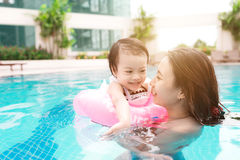 Mother and baby girl having fun in the pool. Summer holidays and Stock Images