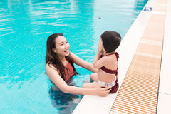 Mother and baby girl having fun in the pool. Summer holidays and Royalty Free Stock Photos