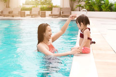 Mother and baby girl having fun in the pool. Summer holidays and. Vacation concept Royalty Free Stock Photos