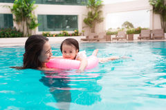 Mother and baby girl having fun in the pool. Summer holidays and Stock Image