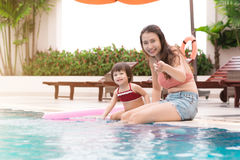 Mother and baby girl having fun in the pool. Summer holidays and. Vacation concept Stock Photos