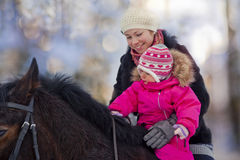 Mother and baby girl horseback riding Stock Photos