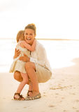 Mother and baby girl hugging on the beach Royalty Free Stock Photography