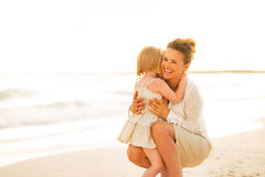 Mother and baby girl hugging on beach Stock Photo