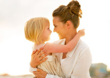 Mother and baby girl hugging on beach Stock Images