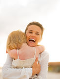 Mother and baby girl hugging on beach Stock Photography