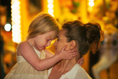 Mother and baby girl hugging in front of carousel Royalty Free Stock Photos