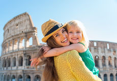 Mother and baby girl hugging in front of colosseum Stock Image