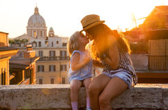 Mother and baby girl kissing in Rome. Mother and baby girl kissing while sitting on street overlooking rooftops of rome on sunset Stock Photography