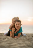 Mother and baby girl laying on beach Stock Photos