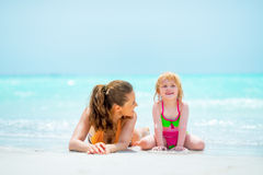 Mother and baby girl laying on beach Stock Photo
