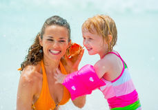 Mother and baby girl listening sound of sea Royalty Free Stock Photos