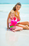 Mother and baby girl listening sound of sea Stock Images