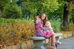 Mother and baby girl making selfie in city park Stock Photo