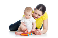 Mother and baby girl play musical toy Royalty Free Stock Images