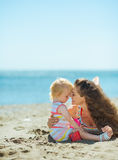Mother and baby girl playing on beach Stock Photos