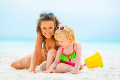 Mother and baby girl playing on beach Stock Images