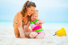 Mother and baby girl playing on beach Royalty Free Stock Image