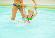Mother and baby girl playing in pool Royalty Free Stock Photo