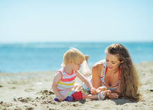Mother and baby girl playing with sand on beach Stock Photo