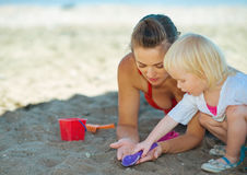 Mother and baby girl playing with sand on beach Royalty Free Stock Photo