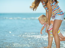 Mother and baby girl playing on sea coast Stock Images