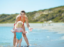 Mother and baby girl playing on sea coast Stock Photos