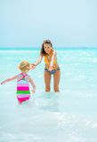 Mother and baby girl playing in sea Royalty Free Stock Photos
