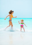 Mother and baby girl playing on sea shore Stock Image