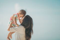 Mother and baby girl playing at seaside Stock Image