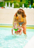 Mother and baby girl playing in swimming pool. Happy mother and baby girl playing in swimming pool stock photo